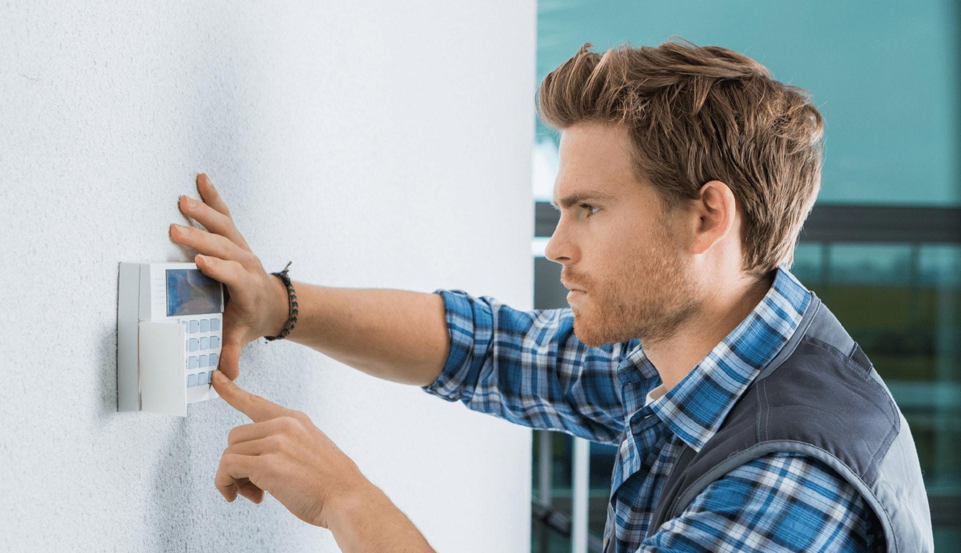 man fitting a burglar alarm