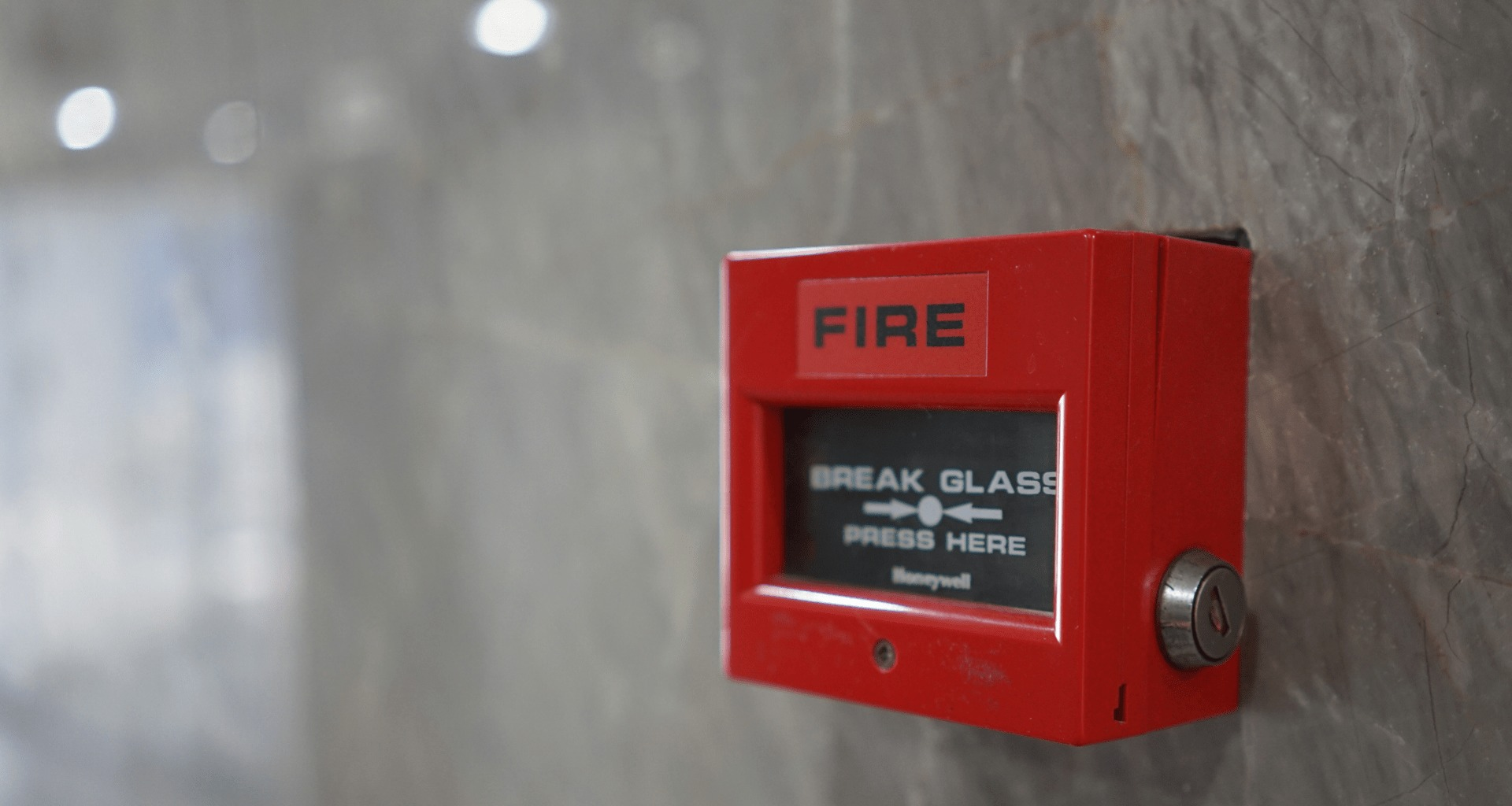 a red wall-mounted fire alarm